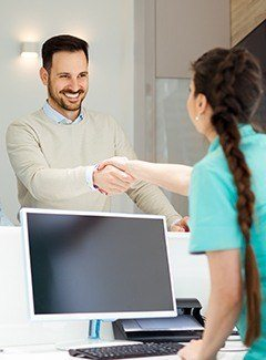 man shaking front desk hand