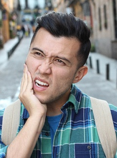 person walking down the street and holding their jaw in pain