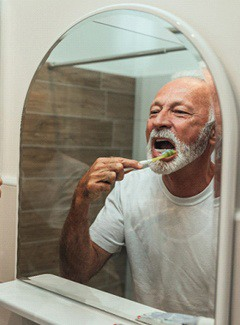 Man brushing teeth to care for dental implants in Topeka