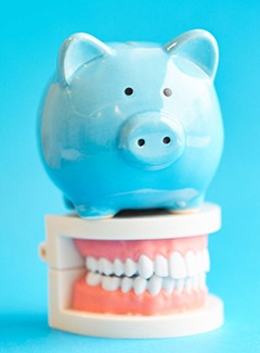 Piggy bank and teeth representing cost of dental implants in Topeka