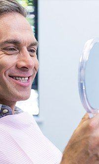 man grinning into mirror