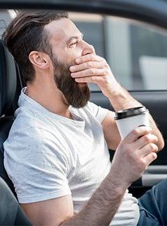 man yawning with coffee in hand