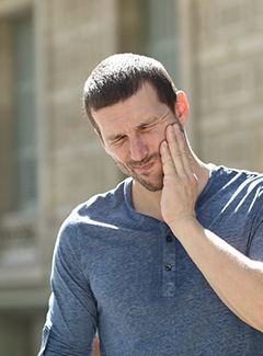 Man in blue shirt suffering from TMJ pain