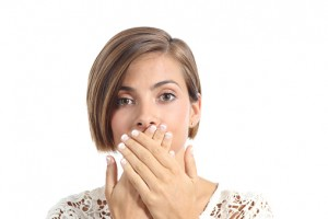 woman covering mouth because of bad breath needs to visit the silver lake dentist