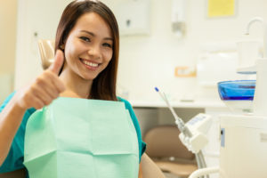 woman giving thumbs up in dental chair